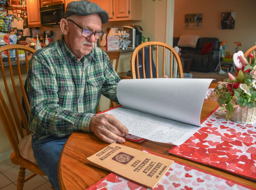 In this Feb. 8, 2019, photo, Ron Best, of Charleston, Ill., looks over a copy of the deed for Abraham Lincoln's 1841 purchase of southern Coles County farm land from his father, Thomas Lincoln. A plot of Illinois farmland once owned by President Abraham Lincoln is heading to auction. Best, a retired farmer in the central Illinois city of Charleston, is selling his family's 590-acre farm, which includes a 30-acre plot once owned by the nation's 16th president. (Dave Fopay/Charleston Times-Courier via AP)