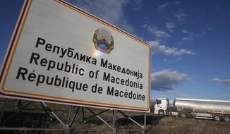 "A tank truck drives by a road sign reading ""Republic of Macedonia"" entering from Greece into Macedonia at Bogorodica border crossing, on Macedonia's southern border with Greece, Tuesday, Feb. 12, 2019.  Macedonian authorities began Monday removing official signs from government buildings to prepare for the country's new name: North Macedonia. (AP Photo/Boris Grdanoski)"
