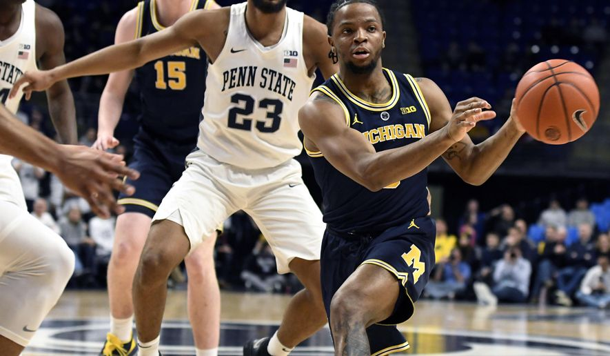 Michigan guard Zavier Simpson (3) passes the ball as Penn State guard Josh Reaves (23) defends during the first half of an NCAA college basketball game, Tuesday, Feb. 12, 2019, in State College, Pa. (AP Photo/John Beale)