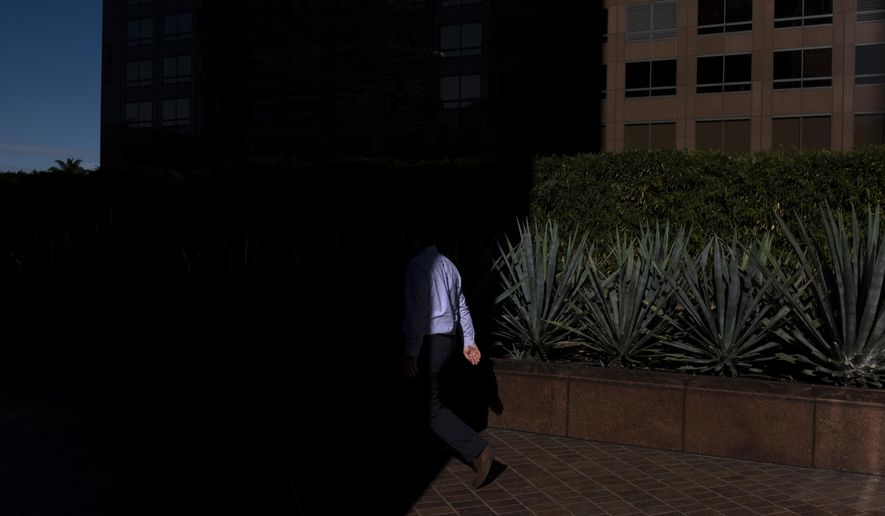 FILE- In this Dec. 4, 2018, file photo a man walks into the shade of a building in downtown Los Angeles. When deciding whether to buy, skip or toss an item, minimalists try to determine whether it adds value to their lives. Apply minimalism to your financial life, and you can shed outdated obligations and reduce stress. (AP Photo/Jae C. Hong, File)