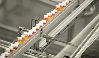 FILE- In this July 10, 2018, file photo bottles of medicine ride on a belt at the Express Scripts mail-in pharmacy warehouse in Florence, N.J. As Democrats in Congress consider whether to back a revamped regional trade pact being pushed by President Donald Trump, they're zeroing in on a new point of conflict: Drug prices. They contend that the new pact would force Americans to pay more for prescription drugs, and their argument has dimmed the outlook for one of Trump's signature causes. (AP Photo/Julio Cortez, File)