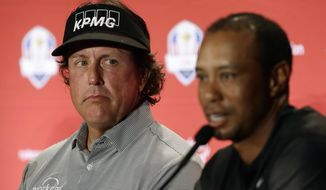 FILE - In this Sept. 4, 2018, file photo, Phil Mickelson, left, listens to Tiger Woods speak during a news conference where they were announced as captain's picks for the 2018 U.S. Ryder Cup Team, in West Conshohocken, Pa. Woods and Mickelson have combined for 124 wins on the PGA Tour, and Mickelson believes they're not done. (AP Photo/Matt Slocum, File)
