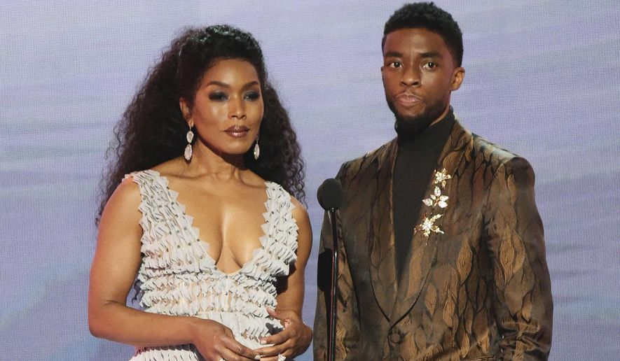 "FILE - In this Jan. 27, 2019, file photo, Angela Bassett, left, and Chadwick Boseman, nominated for outstanding performance by a cast in a motion picture, introduce a clip from their film ""Black Panther"" at the 25th annual Screen Actors Guild Awards at the Shrine Auditorium & Expo Hall in Los Angeles. Boseman and Bassett have been added to the starry list of presenters for the 91st Oscars. (Photo by Richard Shotwell/Invision/AP, File)"