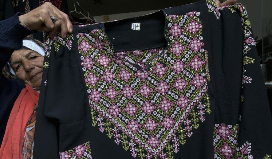 In this Monday, Jan. 28, 2019, file photo, Samiha Jeheshat, displays a handmade embroidered Palestinian thobe at her showroom in the West Bank village of Idna, north of Hebron. The thobe is gaining prominence as a softer symbol of Palestinian nationalism, competing with the classic keffiyeh. Rashida Tlaib proudly wore her thobe to her historic swearing-in as the first Palestinian American member of Congress, inspiring women around the world to tweet photos of themselves in their ancestral robes. (AP Photo/Nasser Nasser)