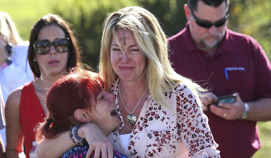 In this Feb. 14, 2018, file photo, Mechelle Boyle, right, embraces Cathi Rush as they wait for news after reports of a shooting at Marjory Stoneman Douglas High School in Parkland, Fla. The image became emblematic of the Parkland school massacre: two terrified moms outside the school, one of them a tall, weeping blonde with the black smudge of Ash Wednesday on her forehead, the other a petite redhead crying in despair on her shoulder. (AP Photo/Joel Auerbach, File)