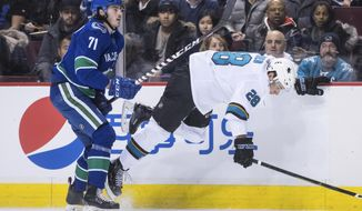 Vancouver Canucks' Zack MacEwan, left, checks San Jose Sharks' Timo Meier, of Switzerland, during the first period of an NHL hockey game in Vancouver, British Columbia, on Monday, Feb. 11, 2019. (Darryl Dyck/The Canadian Press via AP)