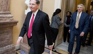 Rep. John Barrasso, R-Wyo., left, and Sen. Rob Portman, R-Ohio, right, walk to a meeting with Republican Senate leadership at the offices of Senate Majority Leader Mitch McConnell of Ky. on Capitol Hill, Monday, Feb. 11, 2019, in Washington. (AP Photo/Andrew Harnik)