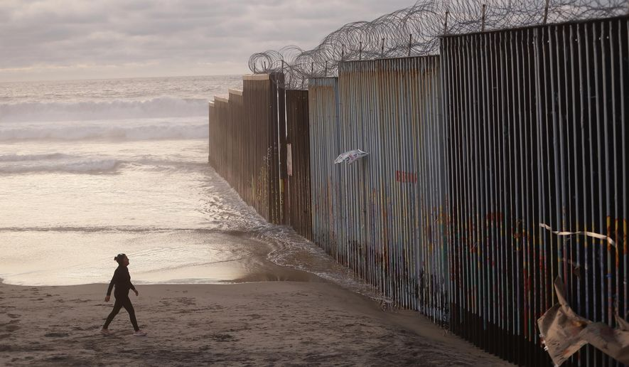 FILE - In this Jan. 9, 2019 file photo, a woman walks on the beach next to the border wall topped with razor wire in Tijuana, Mexico. Congressional negotiators reached agreement to prevent a government shutdown and finance construction of new barriers along the U.S.-Mexico border, overcoming a late-stage hang-up over immigration enforcement issues that had threatened to scuttle the talks. (AP Photo/Gregory Bull, File)