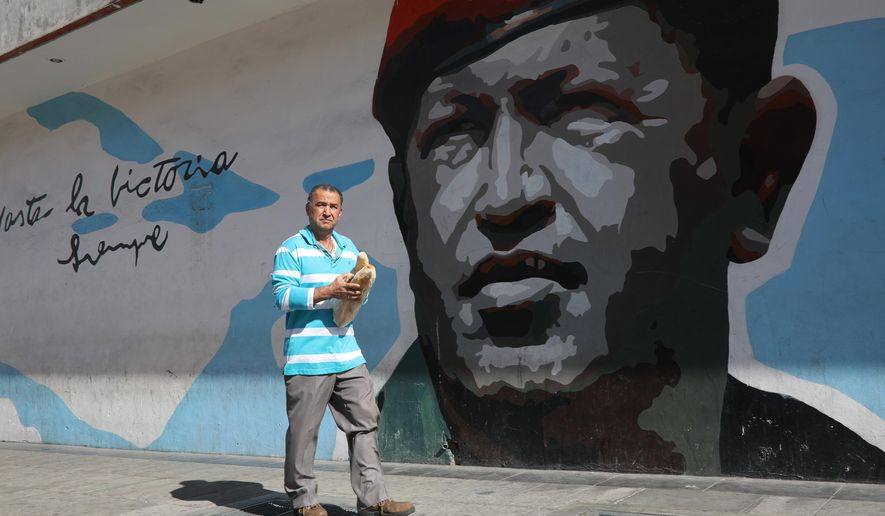 A man walks with a couple loaves of bread past a mural of Venezuela's late former president Hugo Chavez, in Caracas, Venezuela, Tuesday, Feb. 12, 2019. Nearly three weeks after the Trump administration backed an all-out effort to force out Venezuela's President Nicolas Maduro, the embattled socialist leader is holding strong and defying predictions of an imminent demise. (AP Photo/Rodrigo Abd)