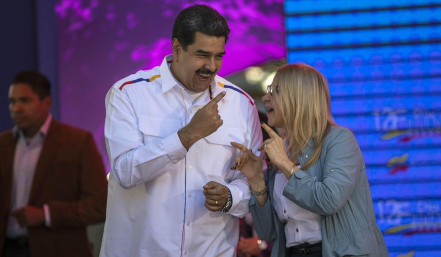 Venezuela's President Nicolas Maduro dances with his wife Cilia Flores, during a pro-government demonstration in Caracas, Venezuela, Tuesday, Feb. 12, 2019.Venezuela's opposition is calling supporters into the streets across the country in a campaign to break the military's support of President Nicolas Maduro. The demonstrations come after more than a month of pressure led by opposition lawmaker Juan Guaido, while Maduro remains firmly in power and at the military's helm. (AP Photo/Rodrigo Abd)