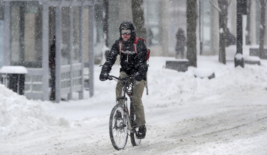 Tom Pearce rides his bike up State Street to his job at the Department of Natural Resources, Tuesday, Feb. 12, 2019, in Madison, Wis. Pearce said it is a three mile trip from home. (Steve Apps/Wisconsin State Journal via AP)