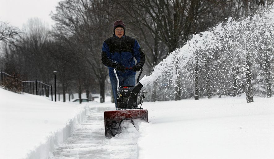 Mike Hahn clears a sidewalk in Wauwatosa, Wis., Tuesday, Feb. 12, 2019. Hahn not only plows the sidewalk in front of his house, but that of several of his neighbors. (Angela Peterson/Milwaukee Journal-Sentinel via AP)