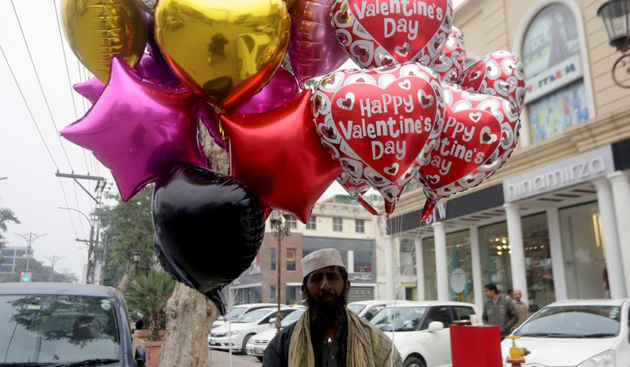 """A Pakistani vendor waits for customers to sell balloons ahead of the Valentine's Day in Lahore, Pakistan, on Wednesday. Celebrating Valentine's Day is considered """"un-Islamic"""" by some in Pakistan, but many still exchange gifts with others. One university has rebranded it as """"Sister's Day"""" and gained notoriety for doing so. (Associated Press)"""