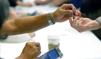 A poll worker checks a photo ID at a Ridgeland, Miss., precinct, Tuesday, Nov. 8, 2016. The is the first presidential election where voters were required to have a photo ID. (AP Photo/Rogelio V. Solis)