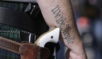 In this Jan. 26, 2015, file photo, a supporter of open carry gun laws, wears a pistol as he prepares for a rally in support of open carry gun laws at the Capitol, in Austin, Texas. Texas is still sorting out where firearms are allowed, and where they're not, more than a year after Republican Gov. Greg Abbott signed a suite of laws that vastly expanded gun rights. (AP Photo/Eric Gay, File)