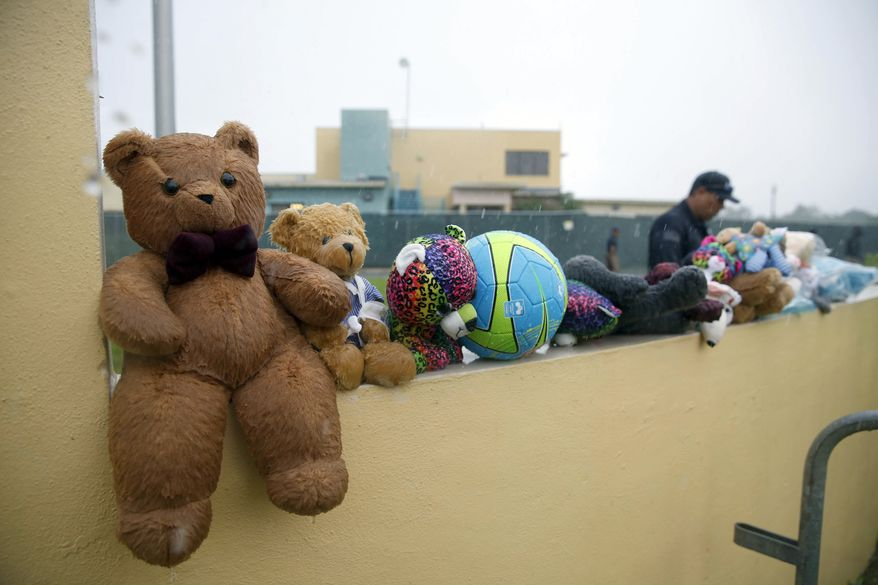 In this June 23, 2018, file photo, a guard walks by toys placed for migrant children by protesters as they march to Homestead Temporary Shelter for Unaccompanied Children, in Homestead, Fla. Journalists were given a glimpse Wednesday, Feb. 13, 2019, of a new expansion at the south-Florida detention facility where nearly 150 teenage migrants sleep in rows of bunk beds in a large windowless room and use portable toilets housed in adjacent tents. (AP Photo/Brynn Anderson, File)