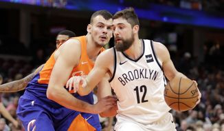 Brooklyn Nets' Joe Harris (12) drives past Cleveland Cavaliers' Ante Zizic (41), from Croatia, in the first half of an NBA basketball game, Wednesday, Feb. 13, 2019, in Cleveland. (AP Photo/Tony Dejak)