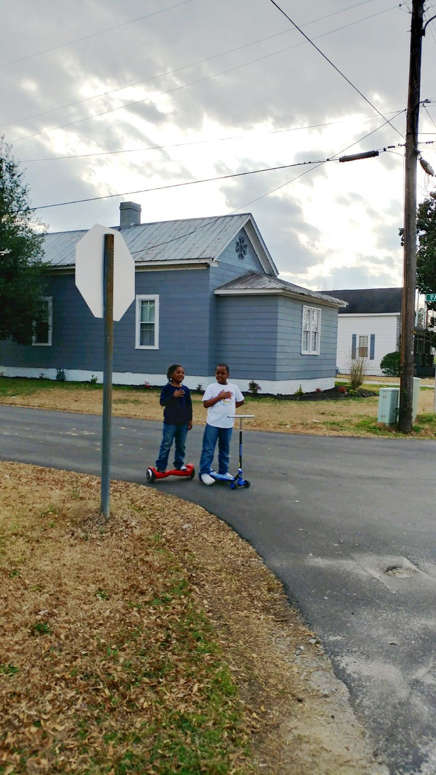 Derrick Ingram, 6, (left) and his 8-year-old cousin Thomas Jones place their hands over their hearts and recite the Pledge of Allegiance as fire department chaplain Bobby Herring raises the U.S. flag in Roseboro, North Carolina, on Feb. 8, 2019. The photo of the two boys was posted on social media, where it has become a viral sensation. (Photograph by Bobby Herring)