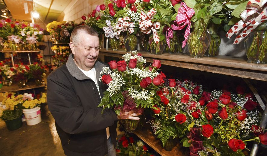 Larry Dominick, who helps out during busy times, looks over some rose bouquets in the flower cooler as he gets orders ready to go out for delivery on Valentine's Day at Welborn Floral & Events in Owensboro, Ky., on Wednesday, Feb. 13, 2019. (Alan Warren/The Messenger-Inquirer via AP)