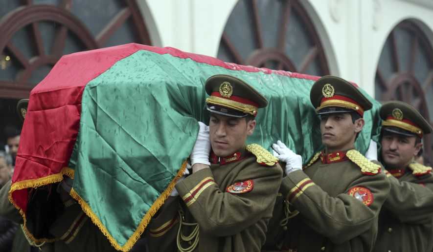 Afghan honor guards carry the coffin of Afghan former president, Sibghatullah Mujadidi during his funeral procession at the presidential palace in Kabul, Afghanistan, Wednesday, Feb. 13, 2019. Afghans are mourning the country's first post-communist president, Sibghatullah Mujadidi, at a palace ceremony attended by his former comrades-in-arms, including his one-time spokesman and protege, former President Hamid Karzai. (AP Photo/Rahmat Gul)