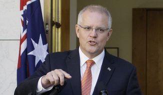 Australian Prime Minister Scott Morrison addresses media at Parliament House in Canberra, Australia, on Wednesday, Feb. 13, 2019. Morrison says his government will reopen a mothballed island detention camp in anticipation of a new wave of asylum seekers arriving by boat after Parliament passed legislation that would give sick asylum seekers easier access to mainland hospitals. (AP Photos/Rod McGuirk)