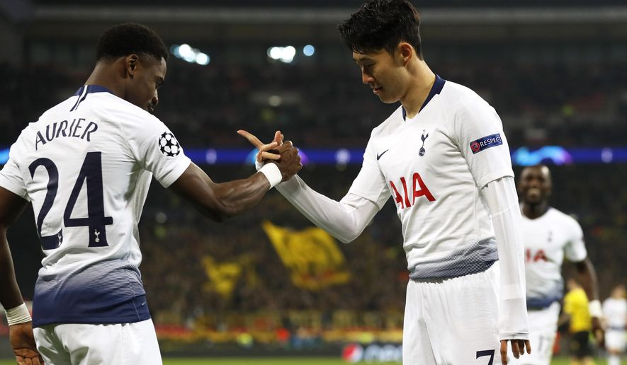 Tottenham midfielder Son Heung-min celebrates with defender Serge Aurier, left, after scoring the opening goal during the Champions League round of 16, first leg, soccer match between Tottenham Hotspur and Borussia Dortmund at Wembley stadium in London, Wednesday, Feb. 13, 2019. (AP Photo/Alastair Grant)