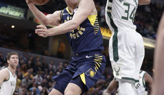 Indiana Pacers forward Bojan Bogdanovic (44) makes a pass around Milwaukee Bucks forward Giannis Antetokounmpo (34) during the first half of an NBA basketball game in Indianapolis, Wednesday, Feb. 13, 2019. (AP Photo/Michael Conroy)