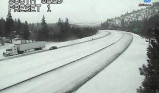 This image from a Caltrans traffic camera shows snow on Interstate 5 in Weed, Calif., Wednesday, Feb. 13, 2019. Rain, snow and wind swept into California on Wednesday, flooding roadways, toppling trees and disrupting travel while bringing renewed threat of mud and debris flows from the state's huge wildfire burn scars. (Caltrans via AP)