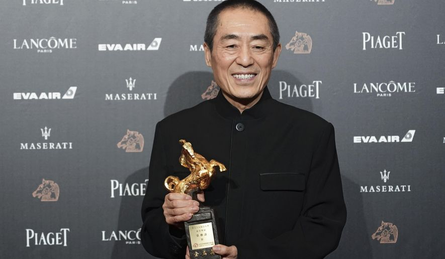 """FILE - In this Saturday, Nov. 17, 2018, file photo, Chinese director Zhang Yimou holds his award for Best Director at the 55th Golden Horse Awards in Taipei, Taiwan. The latest film from Zhang has been dropped from the Berlin International Film Festival for """"technical reasons."""" A notice on the official account of the movie """"One Second"""" on China's Weibo microblogging service apologized, but gave no details other than to say it was not possible to show the film at Berlin. (AP Photo/Billy Dai, File)"""