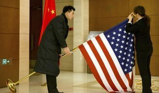 Chinese staffers adjust a U.S. flag before the opening session of trade negotiations between U.S. and Chinese trade representatives at the Diaoyutai State Guesthouse in Beijing, Thursday, Feb. 14, 2019. (AP Photo/Mark Schiefelbein, Pool)