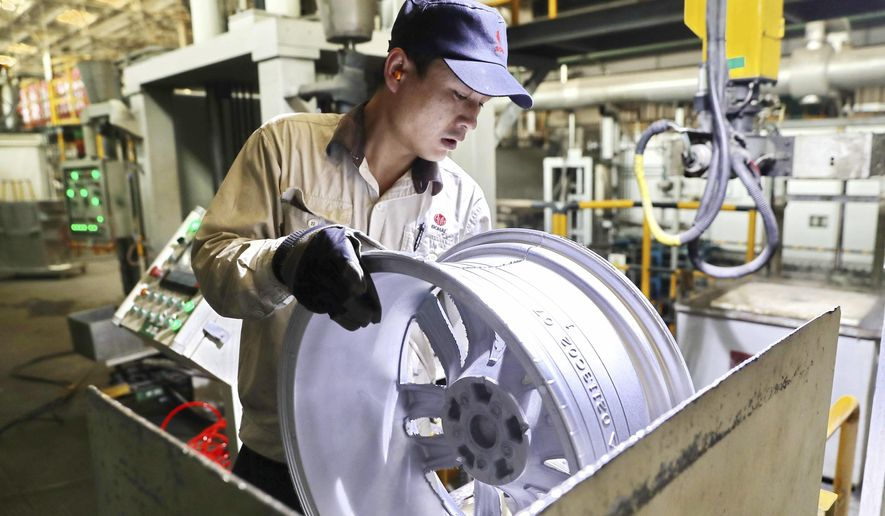 In this Monday, Feb. 11, 2019, photo, a laborer works on an aluminum wheel hub at a manufacturing facility in Qinhuangdao in northern China's Hebei province. U.S. and Chinese negotiators meet this week for their final trade talks before President Donald Trump decides whether to go ahead with a March 2 tariff hike on $200 billion of imports from China. (Chinatopix via AP)