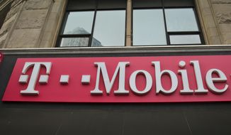 FILE - This April 30, 2018, file photo shows signage a T-Mobile store in New York. The top executives of T-Mobile and Sprint are making the case to Congress that their proposed $26.5 billion merger wouldn't hurt competition and jack up the prices consumers pay for wireless service.  (AP Photo/Bebeto Matthews, File)