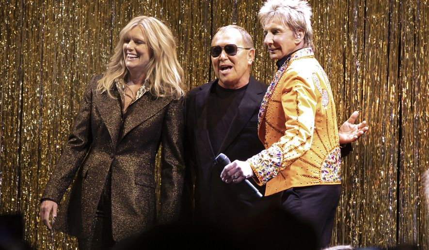 Designer Michael Kors, center, is joined by model Patti Hansen and Barry Manilow on stage after his collection was modeled during Fashion Week in New York, Wednesday, Feb. 13, 2019. (AP Photo/Richard Drew)