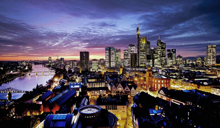 The sun sets over the city of Frankfurt, Germany, with the river Main at left on Tuesday, Feb. 12, 2019. (AP Photo/Michael Probst)