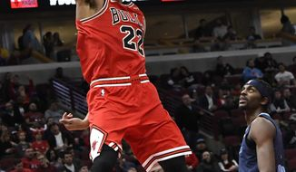 Chicago Bulls forward Otto Porter Jr. (22) dunks the ball as Memphis Grizzlies forward Justin Holiday (7) stands nearby during the second half of an NBA basketball game, Wednesday, Feb. 13, 2019, in Chicago. The Bulls won 122-110. (AP Photo/David Banks)