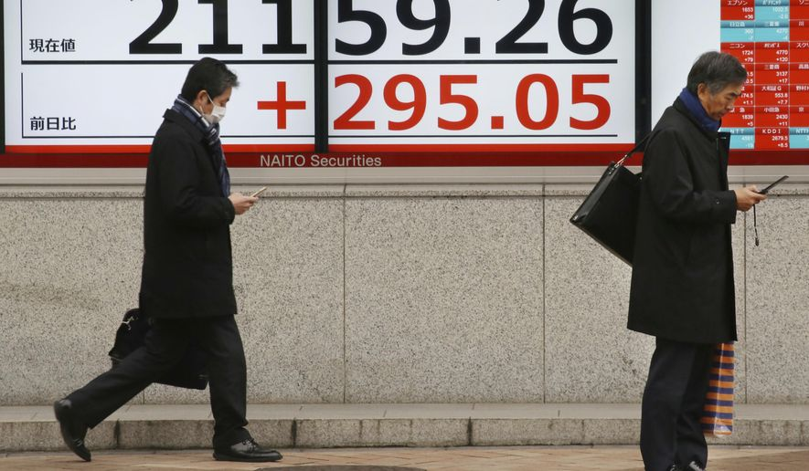 People walk by an electronic stock board of a securities firm in Tokyo, Wednesday, Feb. 13, 2019.  Asian shares were mostly higher Wednesday, cheered by prospects for a resolution to the costly trade dispute between the U.S. and China, which had also sent Wall Street indexes higher. (AP Photo/Koji Sasahara)