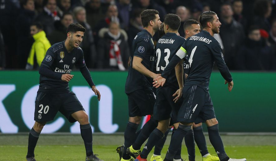 Real midfielder Marco Asensio, left, celebrates after scoring his side's second goal during the first leg, round of sixteen, Champions League soccer match between Ajax and Real Madrid at the Johan Cruyff ArenA in Amsterdam, Netherlands, Wednesday Feb. 13, 2019. (AP Photo/Peter Dejong)