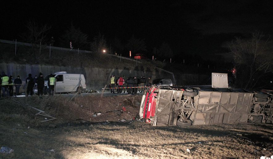 Police and investigators stand near the bus wreckage at the crash site at village of Laskarci, west of Skopje, North Macedonia, Wednesday, Feb. 13, 2019. Macedonia's health minister says some have died and many are injured in the bus crash, carrying workers on a highway west of the capital, Skopje. (AP Photo/Boris Grdanoski)