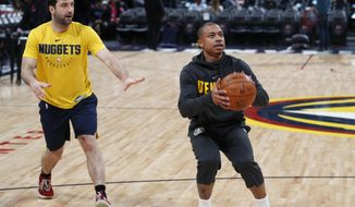 FILE - In this Monday, Feb. 11, 2019, file photo, Denver Nuggets guard Isaiah Thomas takes a practice shot before an NBA basketball game against the Miami Heat in Denver. Thomas, who has been sidelined since last season, may take the court Wednesday, Feb. 13, for the first time as a member of the Nuggets. (AP Photo/David Zalubowski, File)