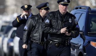 Milwaukee police officers arrive with the public at Oak Creek Assembly of God Church for the public visitation for slain Milwaukee Police Officer Matthew Rittner, Wednesday, Feb. 13, 2019, in suburban Milwaukee. Rittner was killed while serving a search warrant a week ago. Rittner was a U.S. Marine veteran who served two tours in Iraq. (Rick Wood/Milwaukee Journal-Sentinel via AP)