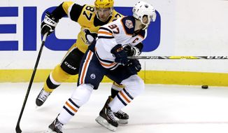 Pittsburgh Penguins' Sidney Crosby (87) defends against Edmonton Oilers' Connor McDavid (97) during the first period of an NHL hockey game in Pittsburgh, Wednesday, Feb. 13, 2019. (AP Photo/Gene J. Puskar)