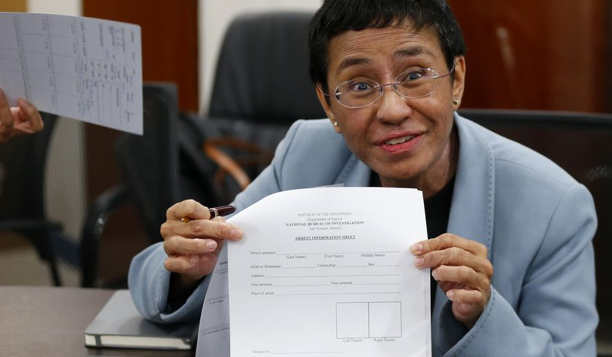 "Maria Ressa, the award-winning head of a Philippine online news site Rappler that has aggressively covered President Rodrigo Duterte's policies, shows an arrest form after being arrested by National Bureau of Investigation agents in a libel case Wednesday, Feb. 13, 2019 in Manila, Philippines. Ressa, who was selected by Time magazine as one of its Persons of the Year last year, was arrested over a libel complaint from a businessman which Amnesty International has condemned as ""brazenly politically motivated."" Duterte's government says the arrest was a normal step in response to the complaint. (AP Photo/Bullit Marquez)"