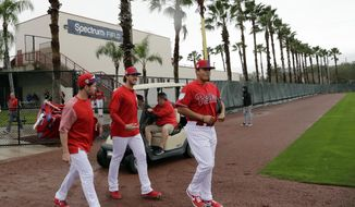 Philadelphia Phillies catcher Andrew Knapp, left, starting pitcher Aaron Nola, center, and relief pitcher Victor Arano, right, walk onto the field at the Philadelphia Phillies spring training baseball facility, Wednesday, Feb. 13, 2019, in Clearwater, Fla. (AP Photo/Lynne Sladky)