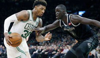 Boston Celtics' Marcus Smart, left, drives for the basket against Detroit Pistons' Thon Maker, right, during the first half of an NBA basketball game in Boston, Wednesday, Feb. 13, 2019. (AP Photo/Michael Dwyer)
