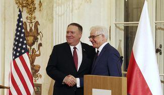 Polish Foreign Affairs Minister Jacek Czaputowicz, right, and U.S. Secretary of State Mike Pompeo shake hands at a news conference at Lazienki Palace, Warsaw, Poland, Tuesday, Feb. 12, 2019. (AP Photo/Czarek Sokolowski)