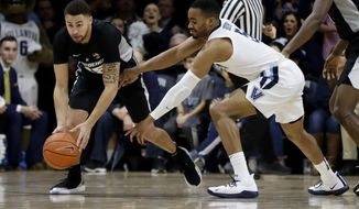 Providence's Drew Edwards, left, and Villanova's Phil Booth chase a loose ball during the first half of an NCAA college basketball game, Wednesday, Feb. 13, 2019, in Villanova, Pa. (AP Photo/Matt Slocum)