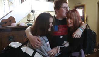 In this, Thursday, Feb. 7, 2019 photo, Matt Deitsch, center, hugs his sister Sam, left, and mother Elizabeth, as Elizabeth prepares to take Sam to the airport on for a speaking engagement in Washington, from their home in Parkland, Fla. Matt, Sam and their brother Ryan have crisscrossed the country helping to register young voters and advocate for stricter gun laws. (AP Photo/Wilfredo Lee)
