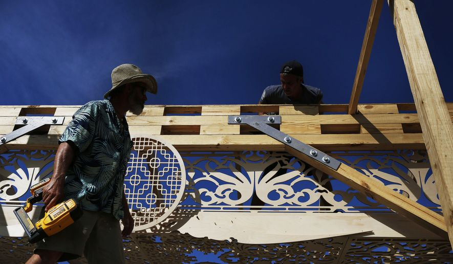 Volunteers help build a California artist, David Best's vision for a non-denominational, temporary temple for the anniversary of the Marjory Stoneman Douglas High School shooting massacre, on Tuesday, Feb. 5, 2019 in Coral Springs, Fla. The temple will remain open until May when it will be burned in a purification ceremony. (AP Photo/Brynn Anderson)