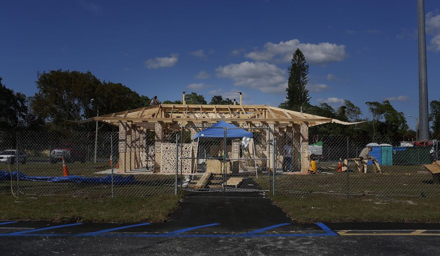California artist David Best, and a team of volunteers build a non-denominational, temporary temple for the anniversary of the Marjory Stoneman Douglas High School shooting massacre, on Tuesday, Feb. 5, 2019 in Coral Springs, Fla. Visitors will be allowed to mourn, remember, contemplate, leave mementos and write message on its walls. (AP Photo/Brynn Anderson)