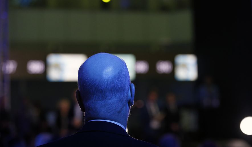 A man watches the ceremony as France's Vinci Airports takes over the running of Belgrade Nikola Tesla Airport in Belgrade, Serbia, Wednesday, Feb. 13, 2019. France's Vinci Airports has formally started a 25-year concession to run Belgrade airport, with massive investment giving the group a foothold in southeastern Europe for its ambitious airport division. (AP Photo/Darko Vojinovic)